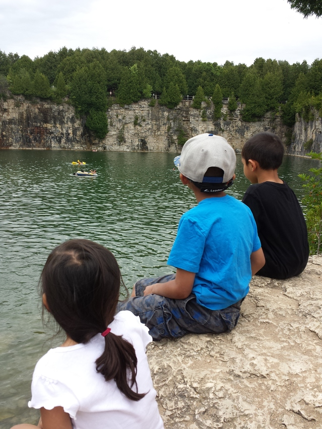 Children sitting on a rock looking out into a quarry