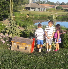 Children playing by pond - a little wooden playhouse beside them