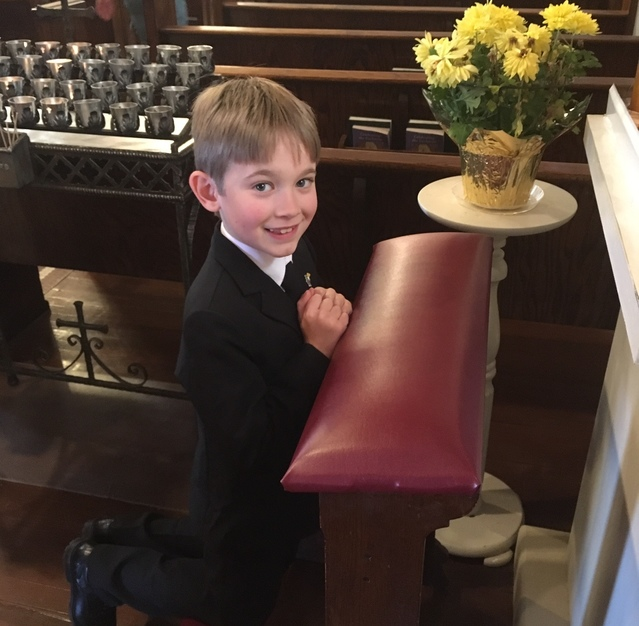Young boy praying in preparation of his first communion