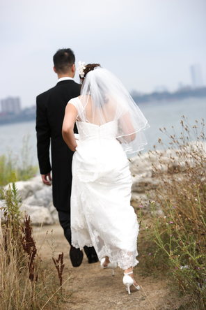 Newly married husband and wife walking along a path towards a a scenic view of a lake