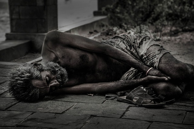 An emaciated and starving man wearing only rags is sleeping on the ground.