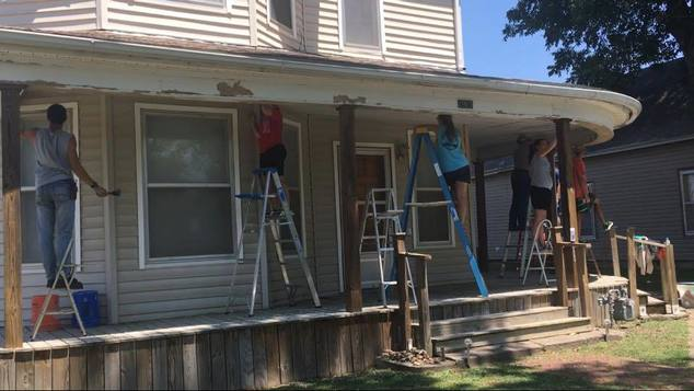 People repairing porch and facade on a house