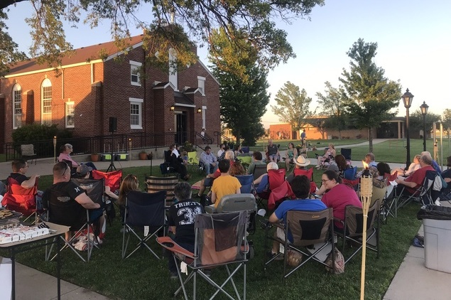 People outside a church on lawn chairs