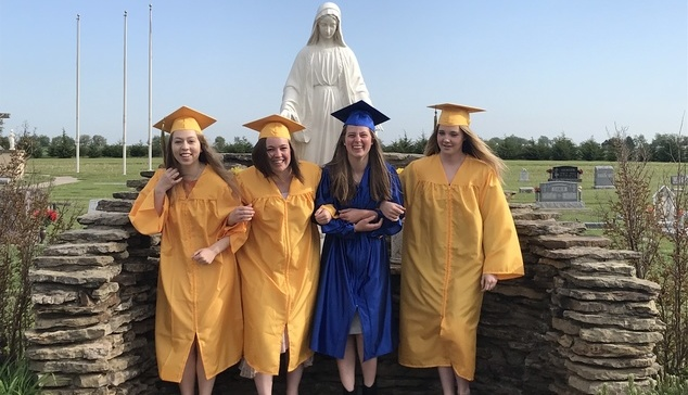 Young women in cap and gown in front of a statue of Our Lady
