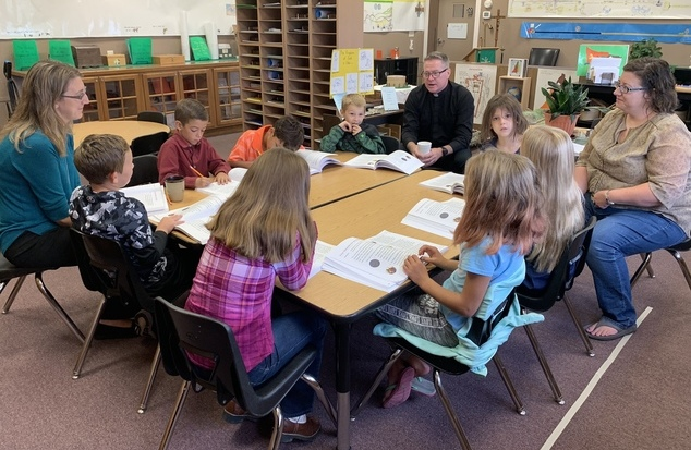 Children, teachers, and Priest in a classroom