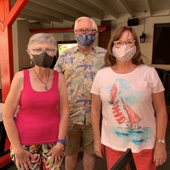 two women and a man in masks