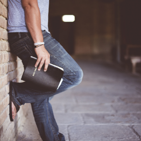 young man with Bible leaning against brick wall