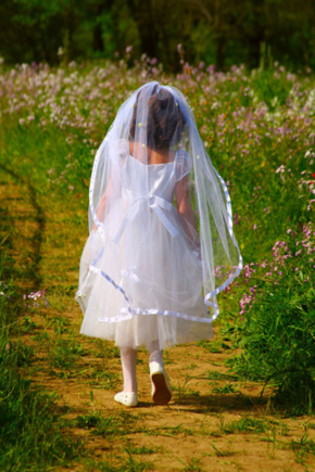 First Communion girl on outdoor path