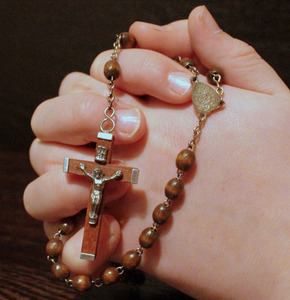 Praying hands holding a rosary