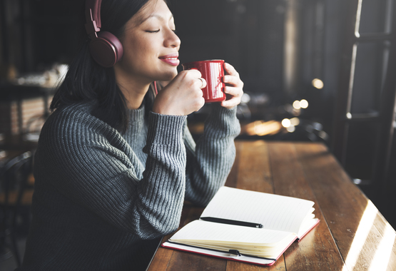 Woman headphones and journal peacefully listening to music.