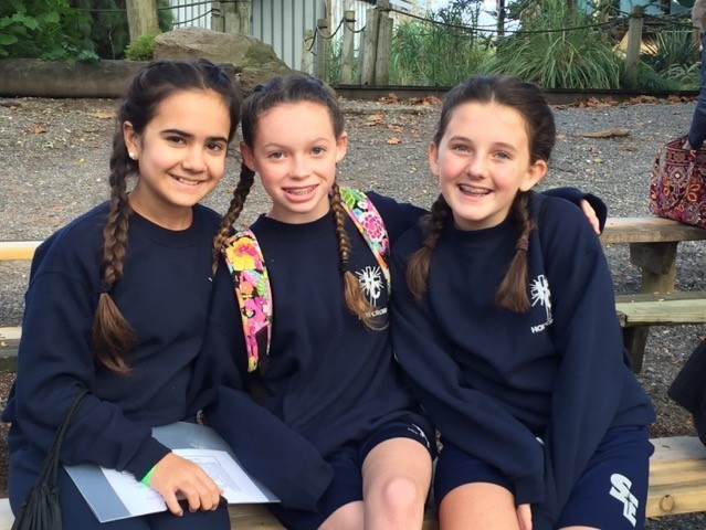 Holy Cross students gather on a bench outside the school building.