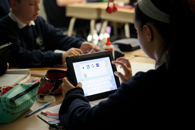 Holy Cross students in class using an electronic tablet