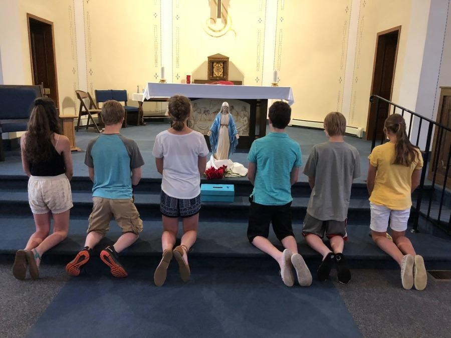 Children kneeling before an statue of Mary