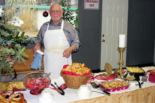 Member of the OLGC Men's Club serves food at reception