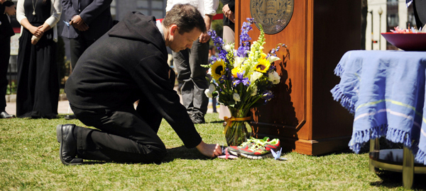 Brother Sam Gunn lays an origami crane in memory of Martin Richard