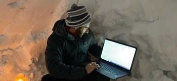 Teacher holds virtual class from inside an igloo