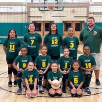 St. John the Baptist School's fourth grade girl's volleyball team picture in the school gym.