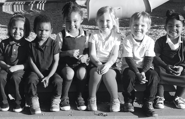 A diverse group of St. John the Baptist Preschoolers sitting in front of the play structure