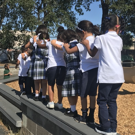 St. John the Baptist School's kindergarten students forming a trust line by the play structure.