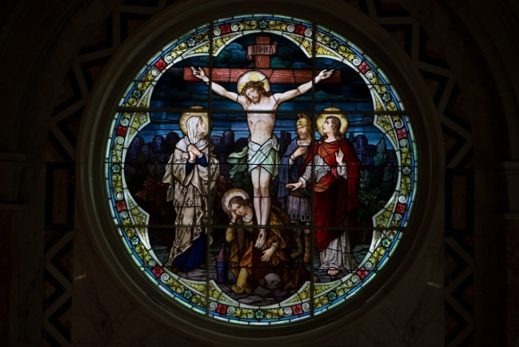 Stain glass picture of Jesus on the cross.