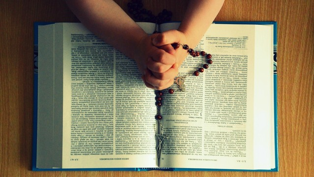 Hands holding a red rosary over the top of an open bible.
