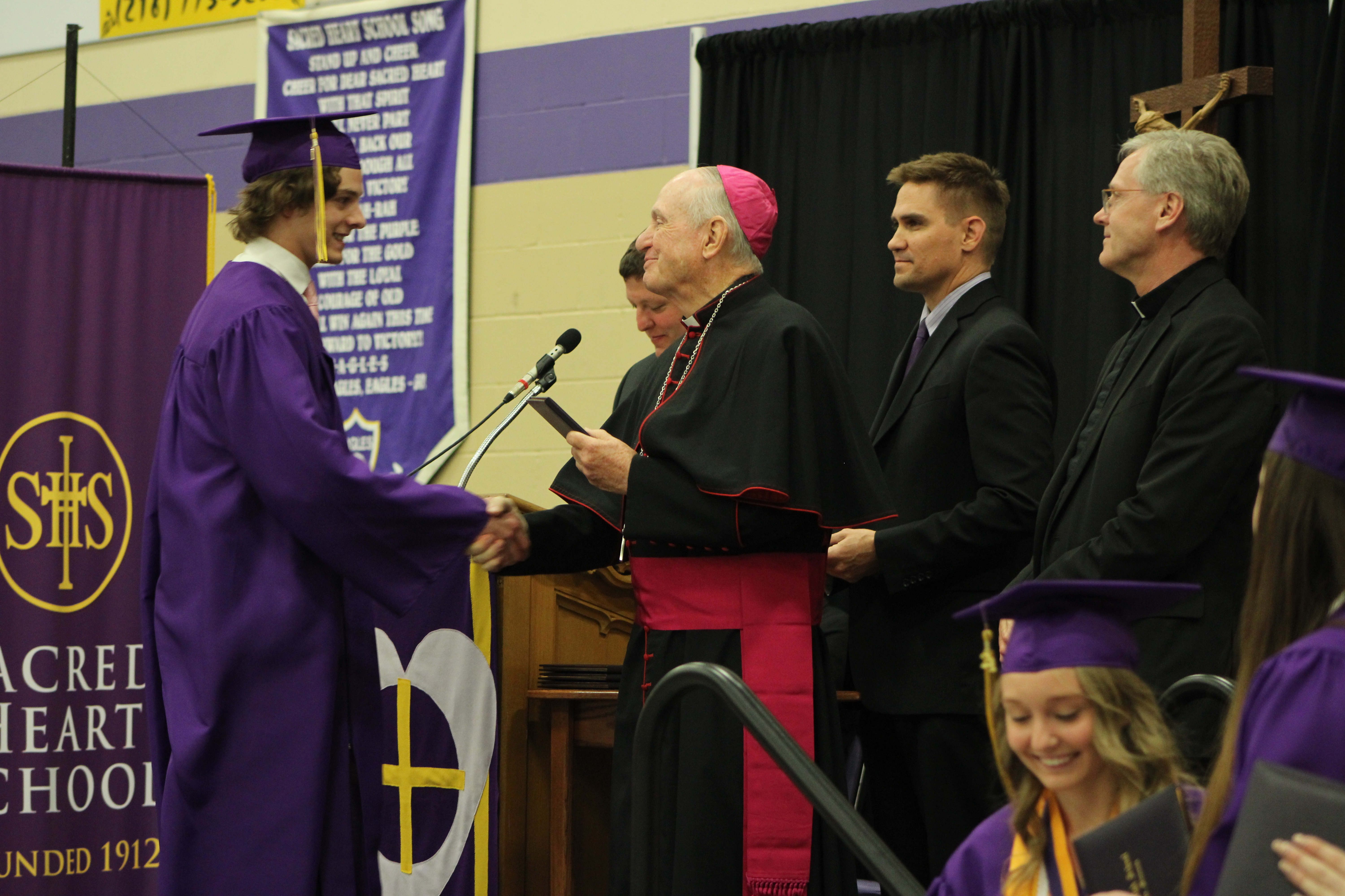 A Sacred Heart graduate receives his diploma at graduation from Bishop Pates,  Apostolic Administrator for the Diocese of Crookston.