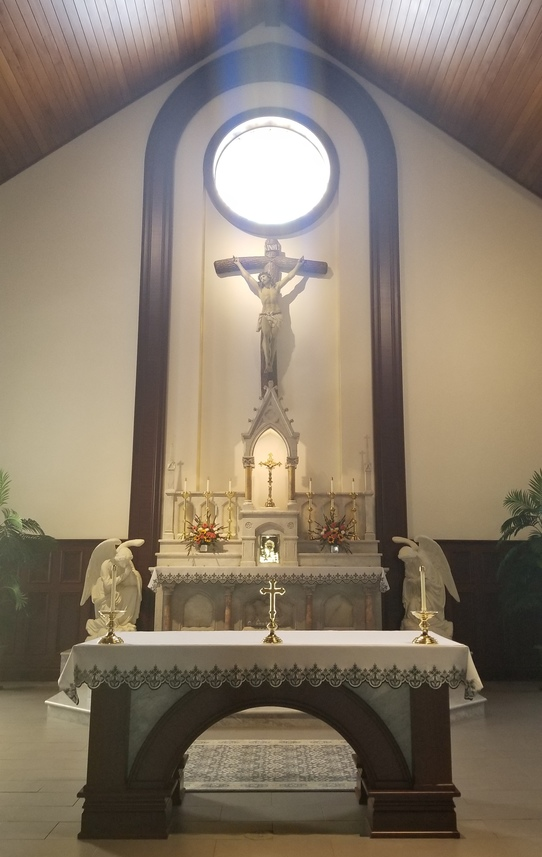 Immaculate Conception Manito wood and marble Altar and traditional marble High Altar with tabernacle light on.