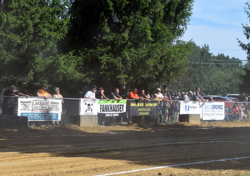 sponsorship banners line the tractor pull fence