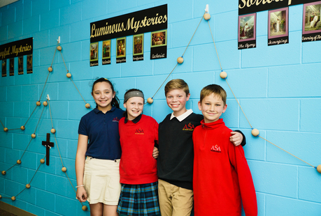 Four middle school students in front of the rosary wall