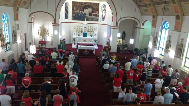 Worshipers celebrate Mass at St. Vincent de Paul prior to heading to the Nationals game.