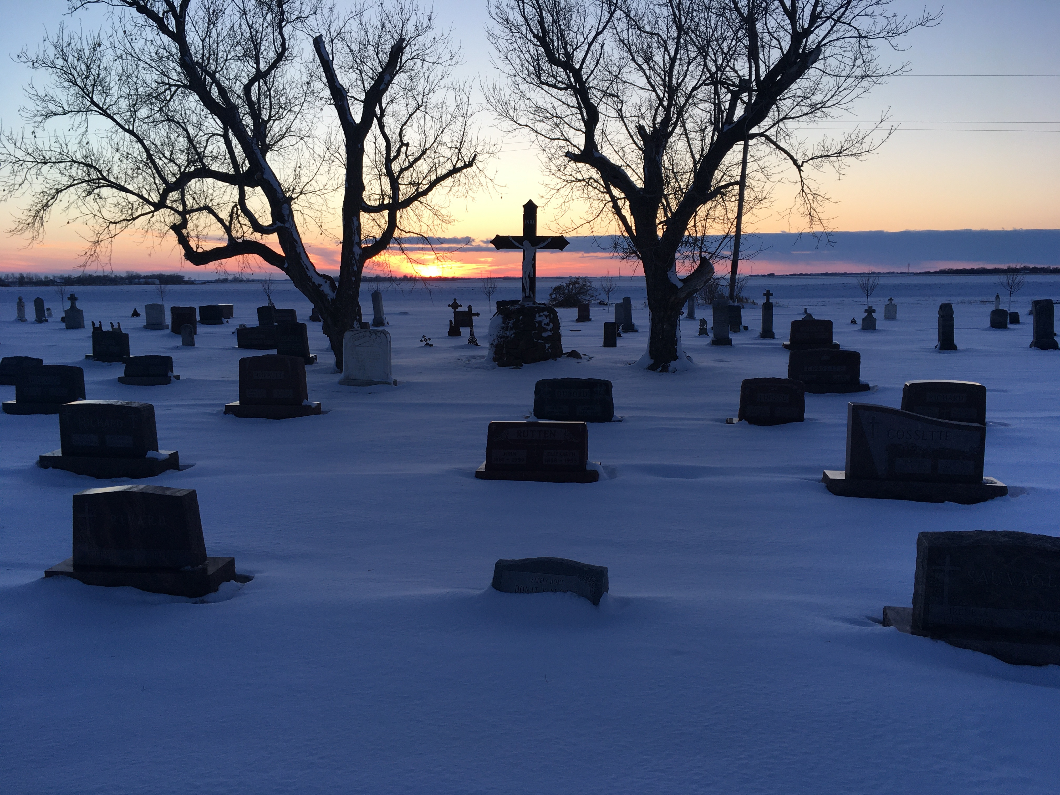 Sunset behind snow-covered tombstones