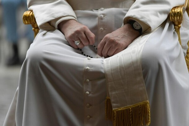 Hands of Pope Francis praying the rosary