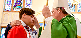 Bishop administers the Sacrament of Confirmation to young people at Passaic church