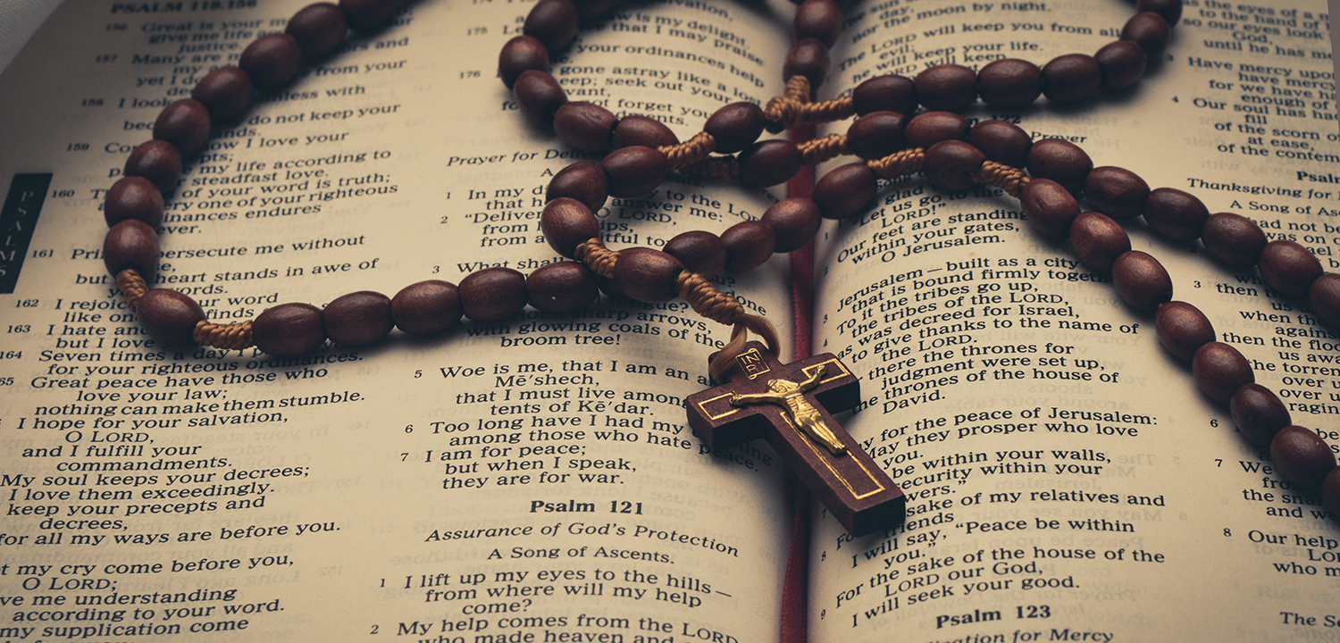 Image of a rosary on an open bible