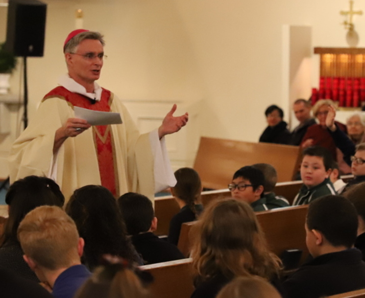 Bishop Daly preaching to children