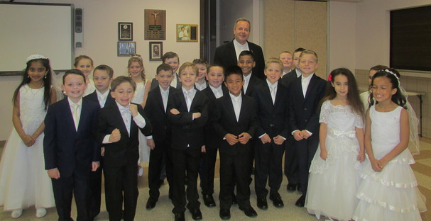 Pastor Vladimir Chripko with some of the boys and girls from the parish Religious Education  Program who received their First Communion on May 7.